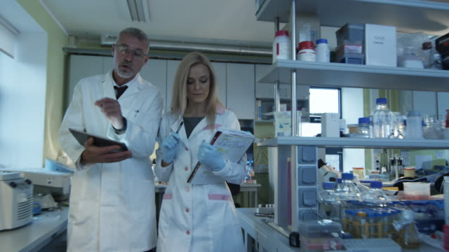 Senior and female scientists with papers and tablet are walking and having a conversation in a laboratory. video