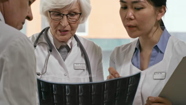 vídeos de stock e filmes b-roll de senior and young female doctors talking to male colleague - sabedoria