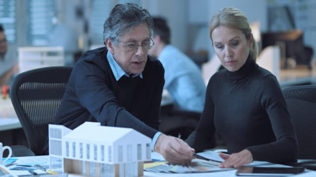 ds senior architect and female colleague discussing interior details - architect stock videos and b-roll footage