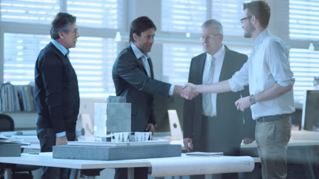 DS Senior architect greeting the investors Medium dolly shot of a senior architect greeting the two business men from the company investing into this project he and his younger colleague are working on. The senior investor is checking the plans and the model they've prepared for them. financial occupation stock videos & royalty-free footage