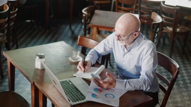 anziano uomo d'affari argentino che fa finanze dietro il laptop nel ristorante - owner laptop smartphone video stock e b–roll