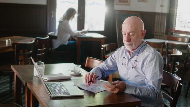 senior argentinian businessman running a local restaurant - owner laptop smartphone video stock e b–roll