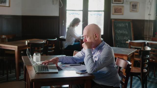 senior argentinian businessman using laptop in the restaurant - owner laptop smartphone video stock e b–roll