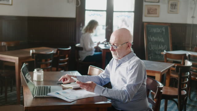 senior argentinian businessman working behind the the laptop during lunch in the restaurant - owner laptop smartphone video stock e b–roll