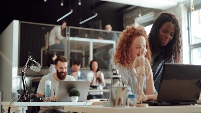 현대 사무실에서 새로운 인턴을 멘토링하는 선임 아트 디렉터 - 문화 스톡 비디오 및 b-롤 화면
