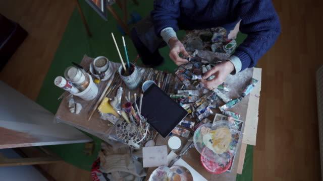 senior artist choosing perfect mix of colors - tavolozza video stock e b–roll