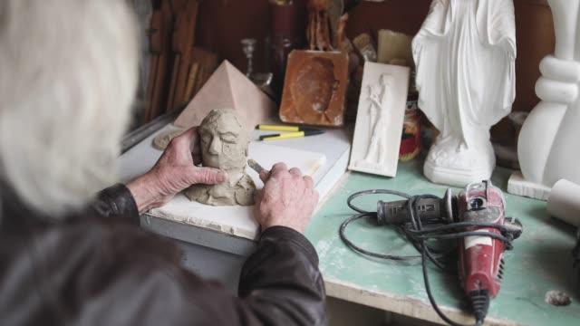vídeos de stock, filmes e b-roll de artista sênior fazendo escultura dentro de casa - arte e artesanato assunto