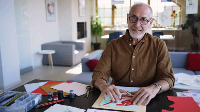 Senior artist posing for a photo at his home office studio video