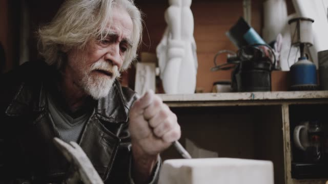 artista senior che lavora con il marmo nel suo laboratorio - scultura video stock e b–roll