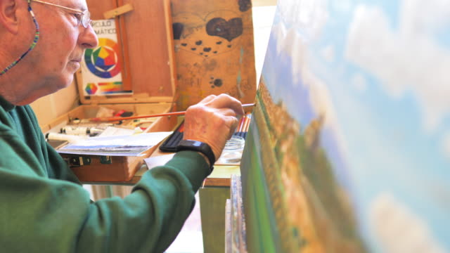 senior artist's hand painting to the oil