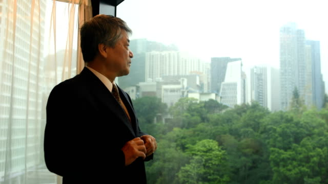 vídeos de stock e filmes b-roll de senior asian businessman getting ready in his hotel - old men window