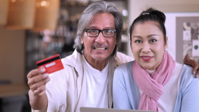 Senior Asian Couple at home glad, celebrate with laptop computer and Credit card, success or happy pose. Financial Transactions,Banking or online shopping concept. Slow Motion