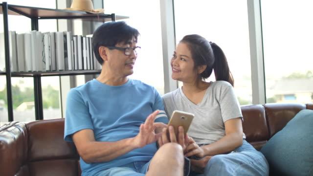 シニアアジアのカップルは一緒にモバイルを使用して愛する - テレビ会議 日本人点の映像素材/bロール