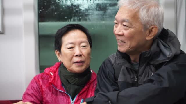 vidéos et rushes de senior couple asiatique prenant transport s'entraînent ensemble. s'amuser sur le voyage de retraite dans le monde entier ensemble - couple marié