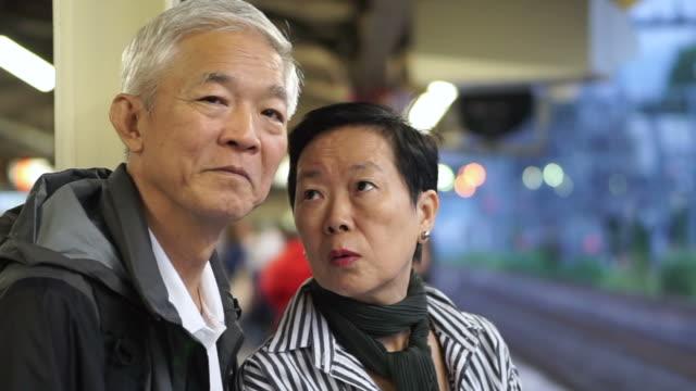 上級アジアのカップルを取って列車輸送を一緒に。一緒に退職の世界旅行を楽しんでください。 - 乗客点の映像素材/bロール
