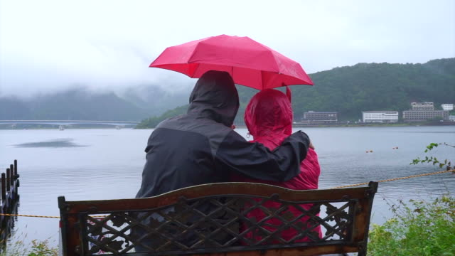 senior asian couple under clear umbrella while travel to cloudy lake, explore the world together after retire - жакет стоковые видео и кадры b-roll