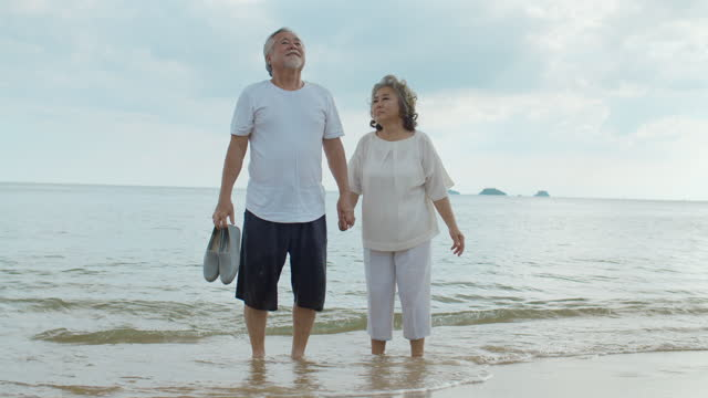 Senior asian couple walking and holding hands at beach,Slow motion