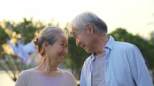 senior asiatische paar zu fuß sprechen im park - aktiver senior stock-videos und b-roll-filmmaterial