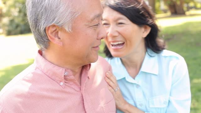 Senior Asian Couple Walking Through Park Together video