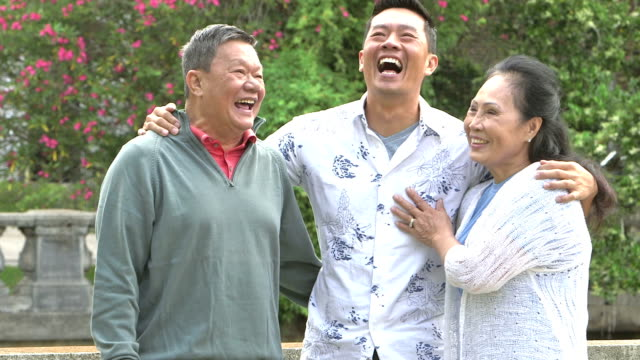 Senior Asian couple with adult son laughing in park video