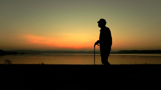 Senior asian male walking with stick at sunset near in the lake , concept healthy, slow motion