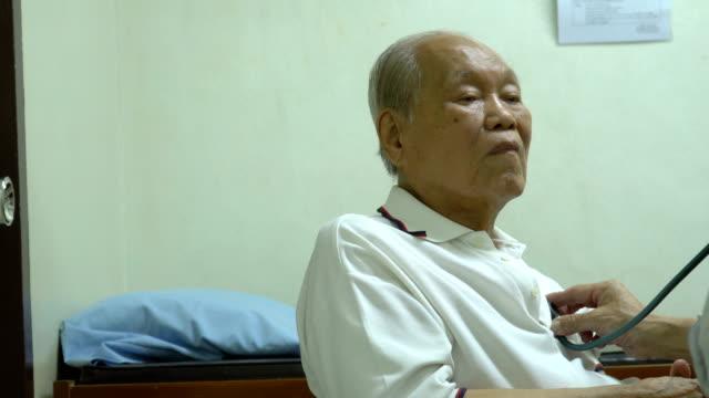 ms rt senior asiatiska man undersöks med stetoskop - kinesiskt ursprung bildbanksvideor och videomaterial från bakom kulisserna