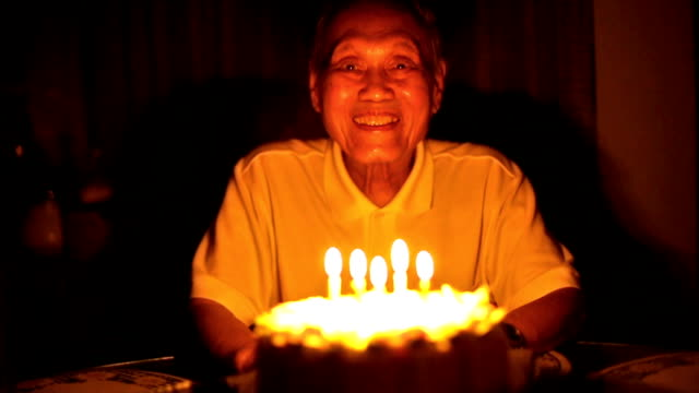 Senior Asian man blows out birthday candles video