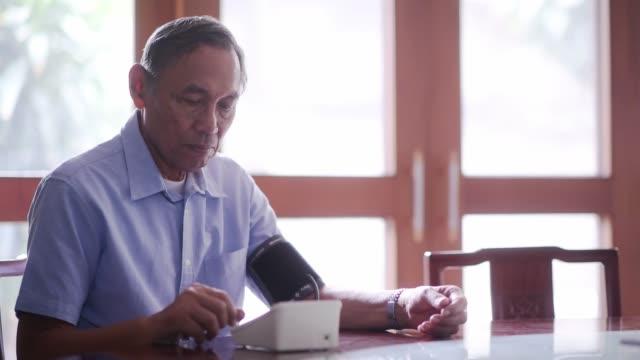 Senior Asian man checking blood pressure Senior Asian man checking blood pressure blood pressure gauge stock videos & royalty-free footage