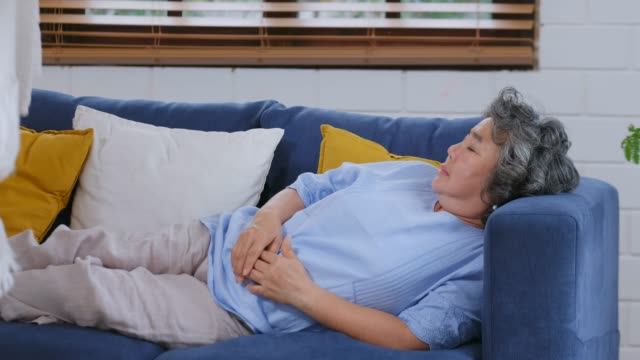 Senior asian man covering his wife with blanket while she sleeping on sofa at home living room, senior couple take care