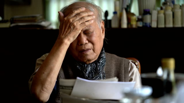 Senior Asian man feeling headache and tired eyes after reading too much