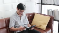 istock Senior Asian man playing tablet and Asian elderly man is Relaxing and Happiness With Video call  on sofa in living room at home 1216076640