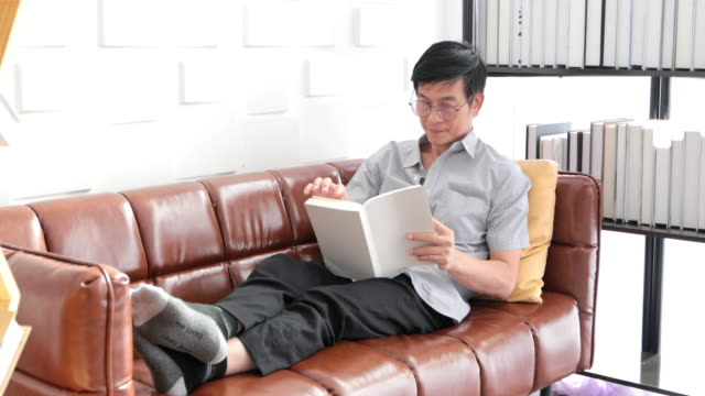 Senior Asian man reading book on sofa in living room at home ,Asian elderly man is Relaxing and Happiness With Read a Magazine