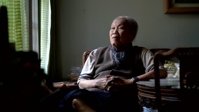 vídeos de stock e filmes b-roll de tu senior asian man sitting near the window and look out side - old men window