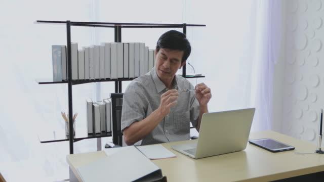 üst düzey bir asyalı adam bir hesap makinesi kullanır ve stresli kadar çok çalışır. - güneydoğu asya stok videoları ve detay görüntü çekimi