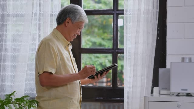senior asian man using digital tablet  with happiness while standing by window at home, daily retirement technology and lifestyle - korzystać z tabletu filmów i materiałów b-roll