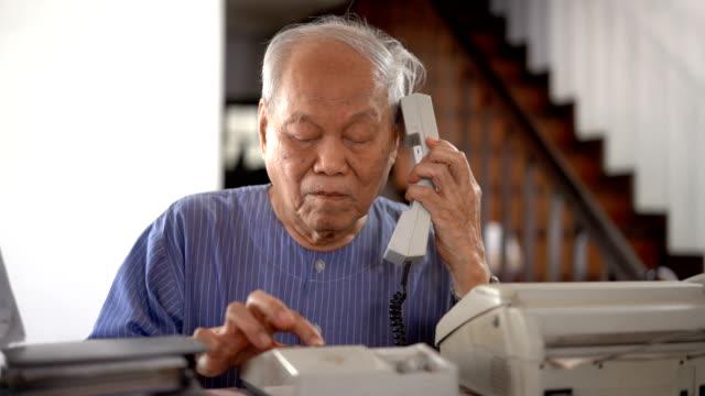 Senior Asian man using retro telephone at home
