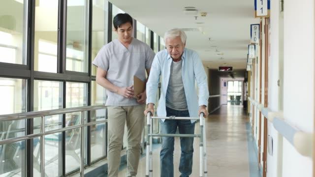 anziano uomo asiatico a piedi con un deambulatore - fragilità video stock e b–roll