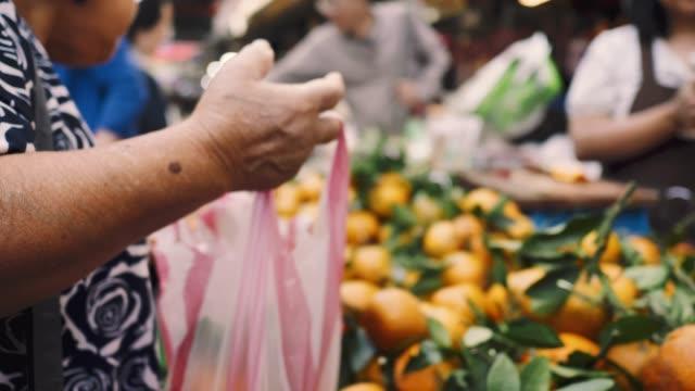 la donna asiatica senior che acquista frutta e verdura si trova al mercato degli agricoltori - mercato frutta donna video stock e b–roll