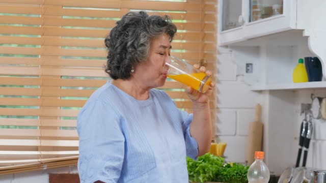 Senior asian woman drinking orange juice in kitchen at home, Retirement lifestyle, Active senior healthy