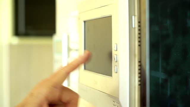 stockvideo's en b-roll-footage met senior aziatische vrouw een code invoert op het toetsenbord van de huisveiligheid alarm. video-intercom naast alarm toetsen. - alarm, home,