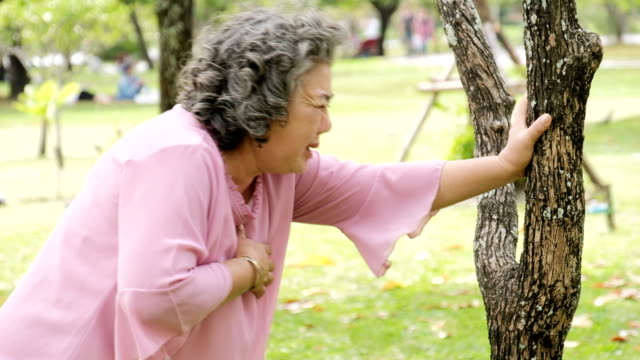 vídeos de stock e filmes b-roll de senior asian woman having heart attack, chest pain - ataque cardíaco