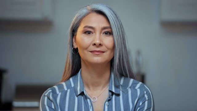 vídeos de stock e filmes b-roll de senior asian woman with grey hair looking at camera - etnia asiática