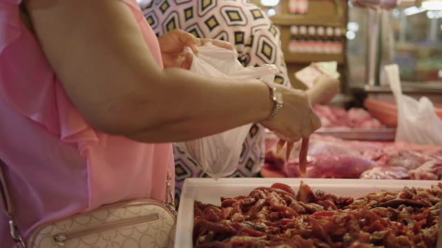 senior asian women choose meat and pork at the market. - essential workers stock videos & royalty-free footage