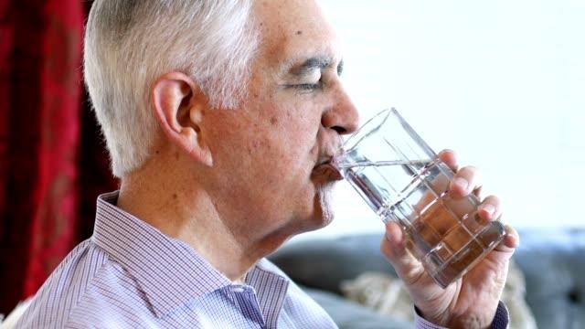 senior at home drinking water - acqua potabile video stock e b–roll