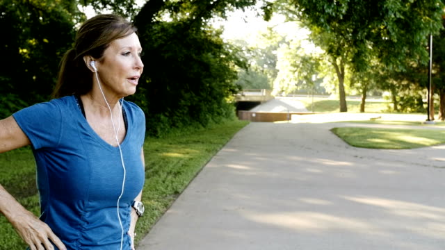 Senior athletic woman jogging on track in park and checking time or pulse video