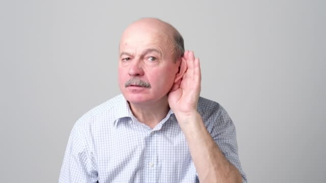 senior bald man listening to gossip about other with hand near ear. - sordità video stock e b–roll