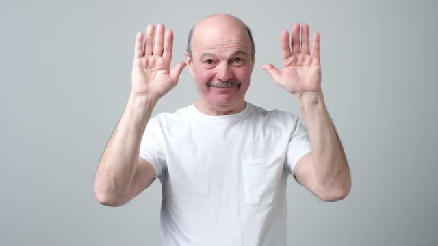 Senior bald man saying bye to his friends waving his hands. Senior bald man saying bye to his friends waving his hands. See you soon guys goodbye single word stock videos & royalty-free footage