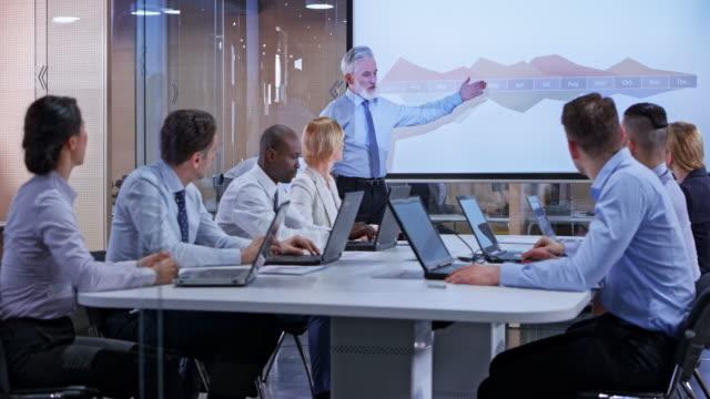 ds-senior bärtigen geschäftsmann hielt eine präsentation für sein team in der glas-konferenzraum - konferenzraum videos stock-videos und b-roll-filmmaterial