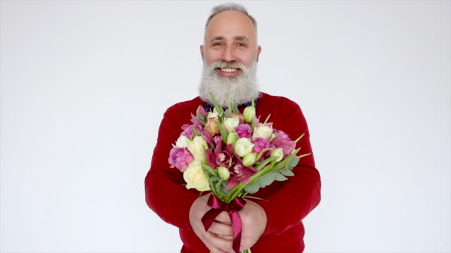 Senior bearded man with flowers on a white background. video