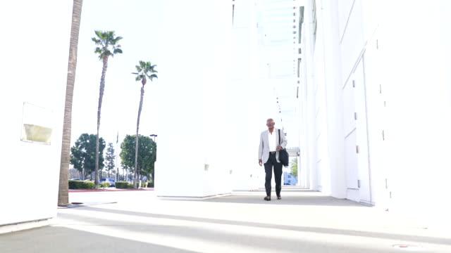 Senior Black Businessman Walking down hallway A senior black businessman using a smartphone baby boomers stock videos & royalty-free footage